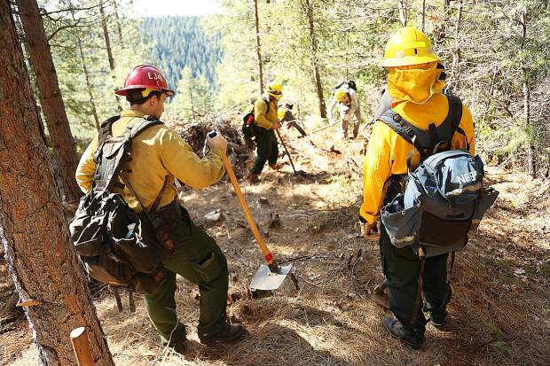Forest service firefighters keep an eye on Work for Warriors participants as they begin to cut a fire break line down a steep hill in the Tahoe National Forest Wednesday.