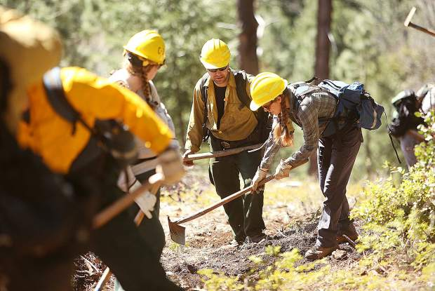 Plumas National Forest firefighter David Dube (center) assists a pair of Work for Warriors participants with tips on how to correctly cut a fire line during Wednesday's wildland firefighter training for veterans at the White Cloud fire station.