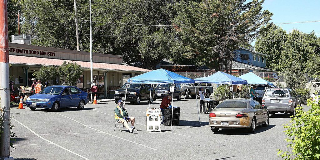 People wait in line during a drive-thru food distribution at Interfaith Food Ministry in Grass Valley.