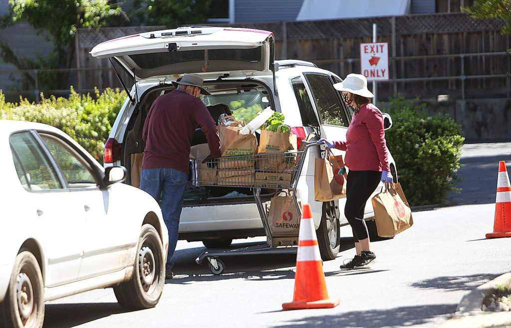 Interfaith Food Ministry's volunteers load a vehicle with food during last Friday's drive-thru distribution.