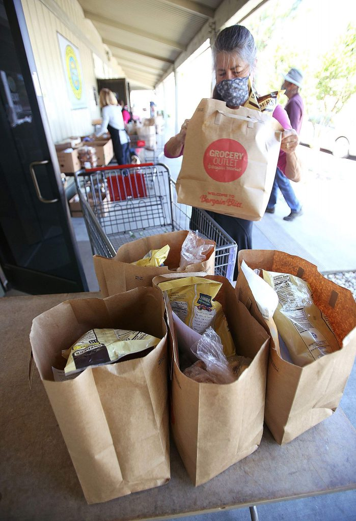 IFM volunteers place a family's order of food on a staging area before being placed into their vehicle.