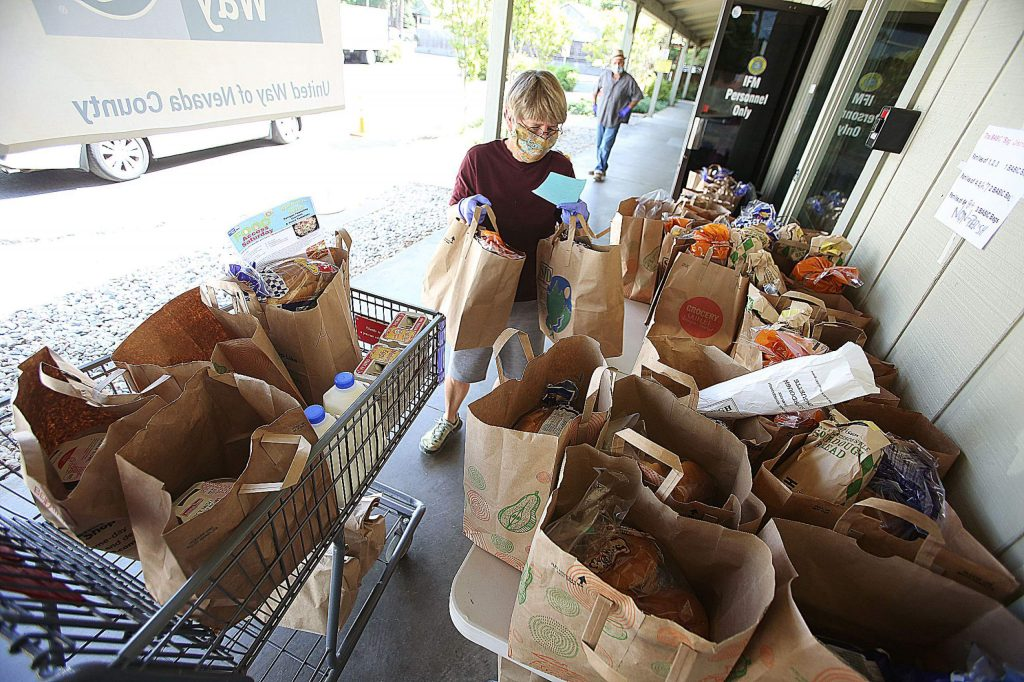 Bear Stillwell checks a list as she gathers food for a large family during a food giveaway.